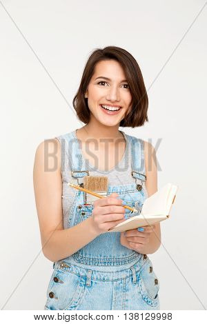 A portrait of young beautiful girl, in gray shirt and denim overall, holding notebook, looking at camera, isolated on white background