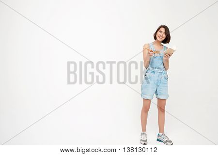 Full length portrait pretty girl, in gray shirt and denim overall, making notes,  pointing forward with finger, isolated on white background
