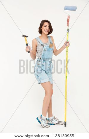 Full length portrait of pretty girl, in gray shirt and denim overall, holding hammer and painting roller, isolated on white background