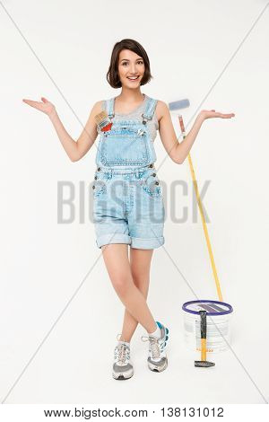 Full length portrait of happy pretty girl, in gray shirt and denim overall, gesturing with her hands, crossed legs, isolated on white background