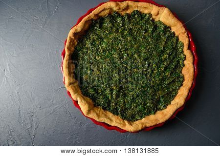 Close-up photo of baked tart dough with spinach in red ceramic tart pan, over gray textural surface
