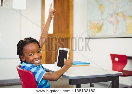 Portrait of happy schoolboy sitting on chair with digital tablet in classroom at school