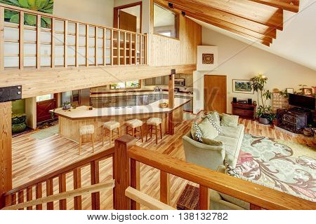 View From The Staircase Into The Living Room And Kitchen Room. Wooden Beams On The Ceiling.