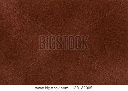Dark brown suede fabric closeup. Velvet texture background