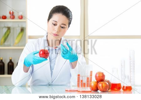 Researcher And Microscope With A Gmo Apple