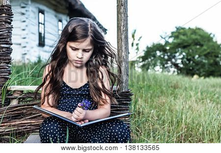 little girl reading an interesting book sitting next to the house