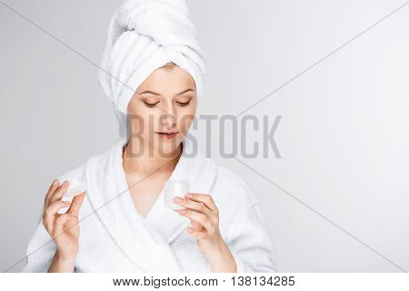 Portrait of blonde young pretty girl in bathrobe with towel on head, opening cream, over white background.