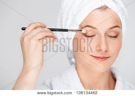 Portrait of blonde young pretty girl in bathrobe with towel on head doing make-up with brush, smiling, eyes closed, over white background.