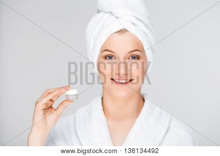 Portrait of blonde young pretty girl in bathrobe with towel on head, holding cream in hand, smiling, looking at camera, over white background.
