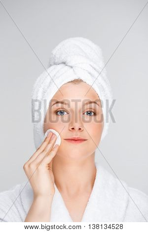 Portrait of blonde young pretty girl in bathrobe with towel on head washing off make-up, looking at camera, over white background.
