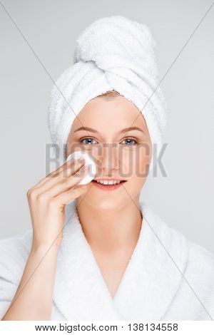 Portrait of blonde young pretty girl in bathrobe with towel on head washing off make-up, smiling, looking at camera, over white background.
