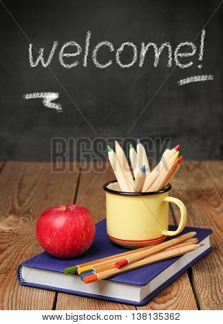 Still life, business, education concept. Pencils in a mug, books and apple on a wooden table, chalkboard with welcome school text. Selective focus, copy space background