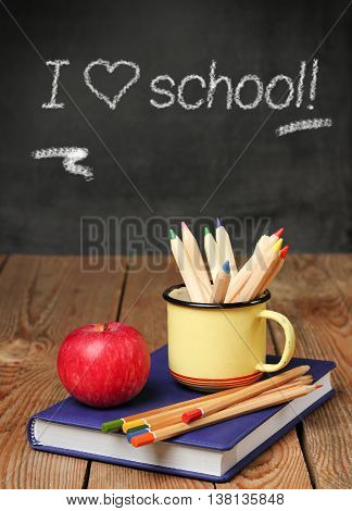 Still life, business, education concept. Pencils in a mug, books and apple on a wooden table, chalkboard with love school text. Selective focus, copy space background