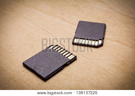 black SD memory card on wood texture