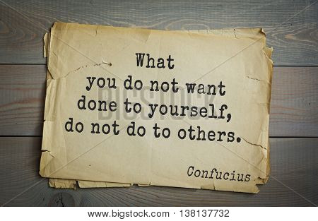 Ancient chinese philosopher Confucius quote on old paper background. What you do not want done to yourself, do not do to others.