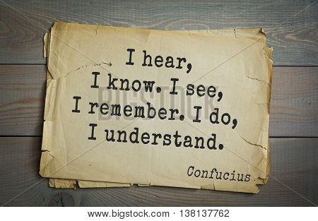 Ancient chinese philosopher Confucius quote on old paper background. I hear, I know. I see, I remember. I do, I understand.