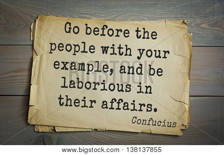 Ancient chinese philosopher Confucius quote on old paper background. Go before the people with your example, and be laborious in their affairs.