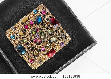 Vintage golden brooch in black jewel box as a background