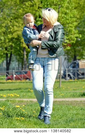 Mother walking with son.Carries son in her arms. Summer in the Park.