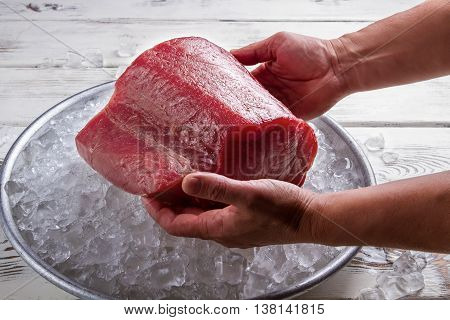 Male hands hold fish meat. Plate with ice and meat. Huge piece of tuna. Don't spoil the food.