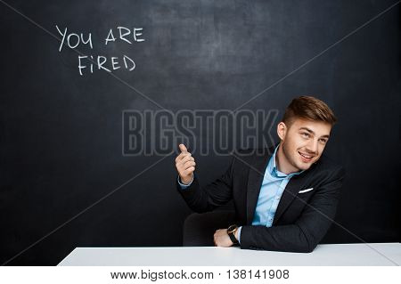 image of young suited man point with  finger at the inscription over blackboard with a text you are fired. looking right