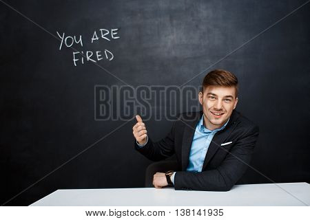 image of young suited man point with  finger at the inscription over blackboard with a text you are fired. looking foward