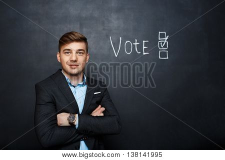 picture of suited man, standing and smiling near text vote over blackboard