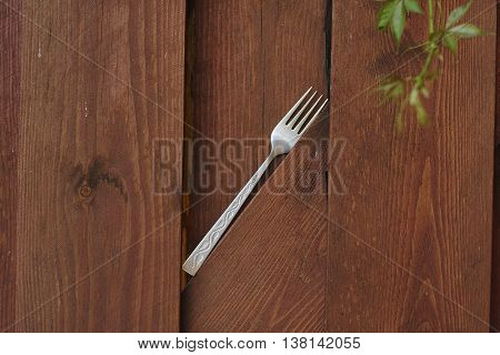 silver fork on red lumber fence diagonal close up