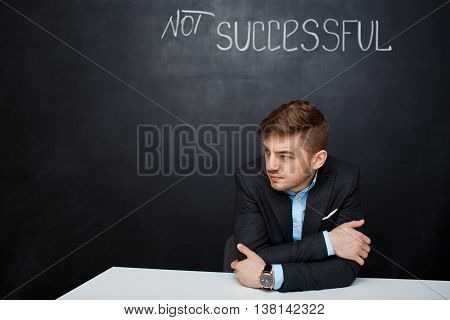 Picture of a  suited, sad man over black board with a text successful. Looking left.