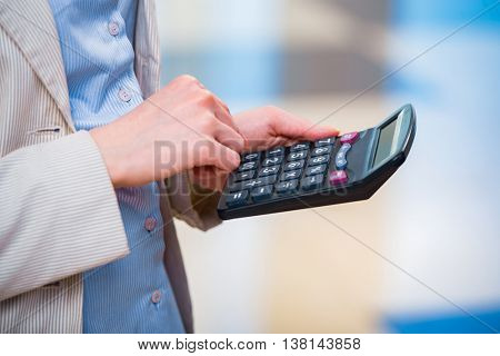 Hands calculating profit on the calculator