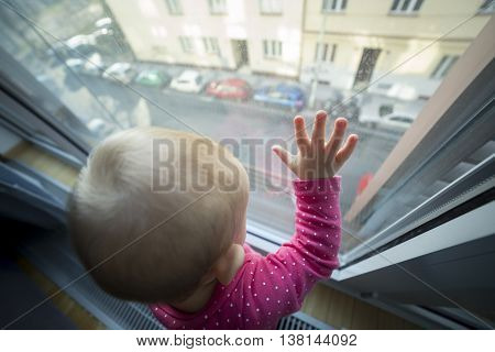 sad lonely child looking out the window in the rainy weather with her hands on the glass