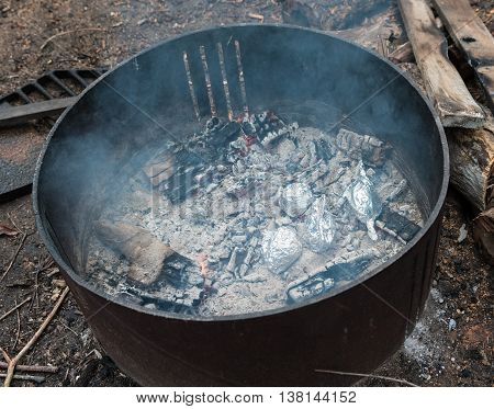 Potatoes wrapped in foil cooking on coals in camp fire