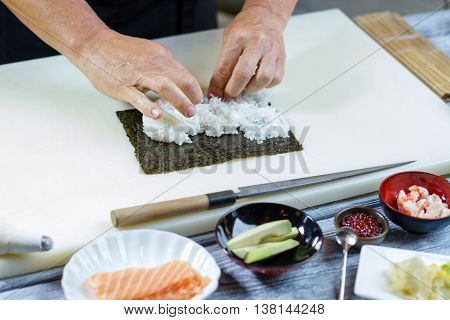 Man's hands touch rice. Knife near bowl with avocado. Filling for uramaki rolls. Skillful sushi chef at work.