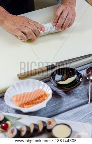 Man's hands touch sushi roll. Beige cooking board and knife. How to prepare uramaki rolls. Chef busy in restaurant kitchen.