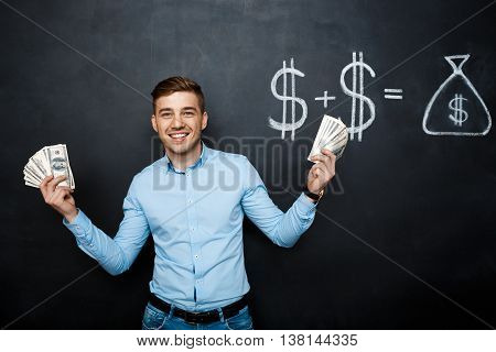 handsome man standing over blackboard. Holding dollars in his hands and smiling