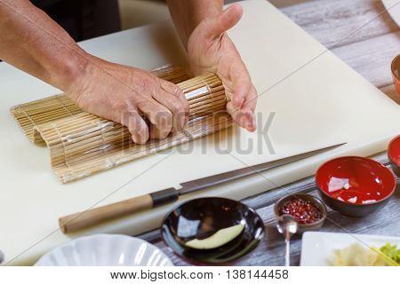 Male hands hold bamboo mat. Knife lying near bamboo mat. Skillful chef of sushi cafe. Culinary traditions of Japan.