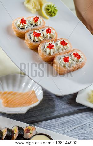 Sushi and wasabi with lemon. Sushi rolls lying on plate. New japanese dish in menu. Uramaki rolls with incredible taste.