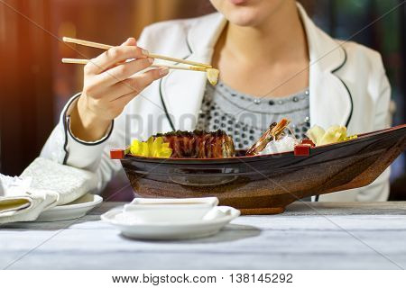 Woman's hand holds chopsticks. Small slice of ginger. Lover of japanese cuisine. Lady ordered uramaki rolls.