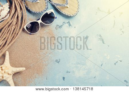 Beach accessories. Sunglasses, flip-flops and sea shells on stone background. Top view with copy space. Sunny toned