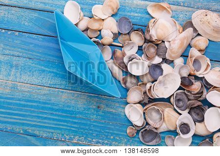 Paper Boat with shells. On blue wooden planks background