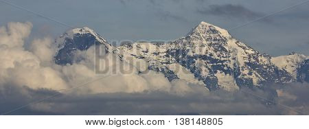 Famous mountains Eiger and Monch surrounded by clouds. Scene in the Swiss Alps.