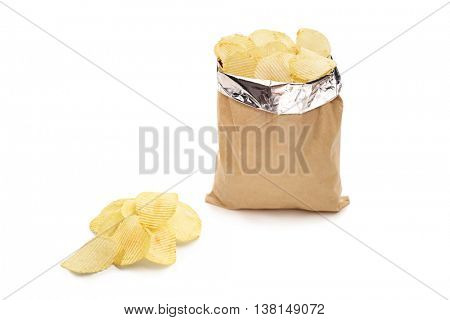 Studio shot of a bag of potato chips and a pile of chips next to it isolated on white background