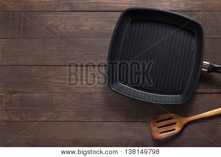 Cast Iron Frying Pan And Spatula On The Wooden Background. Copy Space For Your Text