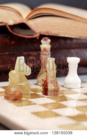 Set of chess pieces made from Onyx on board near book