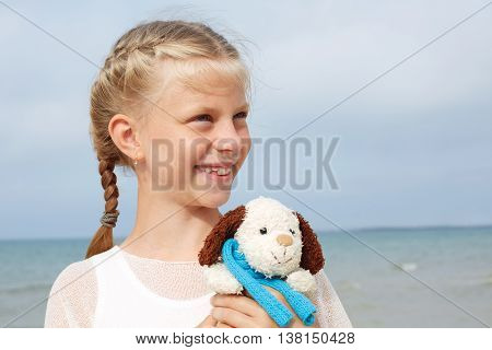 Children psychology. The little beautiful girl embraces an amusing dog - toy. Favorite soft toy.