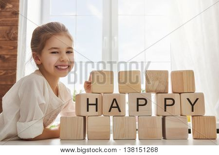Cute girl playing with blocks and having fun. Blocks have letters. The child puts the word happy.