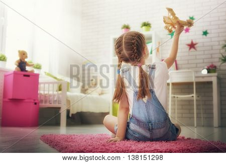 happy child little girl playing with toy airplane at home.