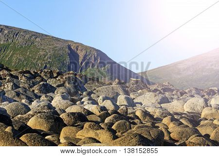 Round stones on a background of mountains, the ocean, Norway, Scandinavia, Travel with sunny hotspot