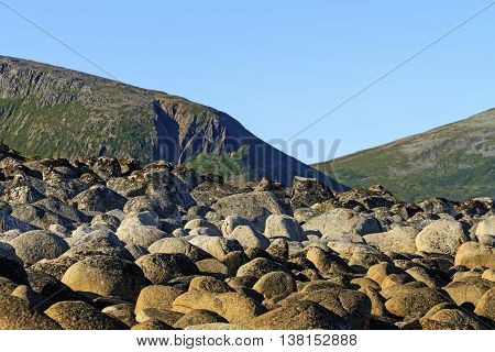 Round stones on a background of mountains, the ocean, Norway, Scandinavia, Travel