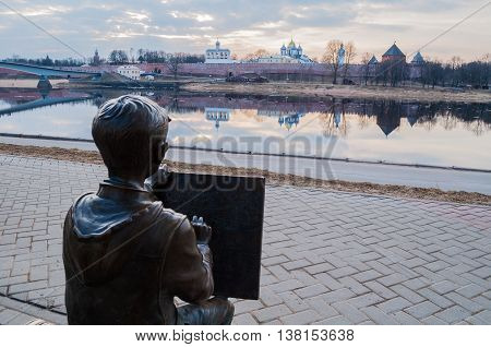 VELIKY NOVGOROD RUSSIA -MARCH 26 2016. Architecture landscape spring view - sculpture of the painter boy drawing the Novgorod Kremlin in front of the Volkhov river in Veliky Novgorod Russia